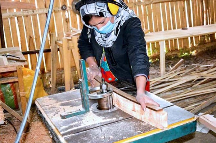 HUNZA: October 05 - A lady carpenter busy in cutting wood through machine to make furniture at CIQAM Women Social Enterprise near Altit fort. APP photo by Ashraf Hussain Nasiri