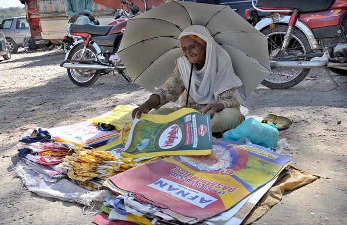 ISLAMABAD: October 06 - An elderly female vendor displaying plastic bags to attract the customers in front of weekly Tuesday Bazaar at Peshawar More. APP photo Saeed-ul-Mulk