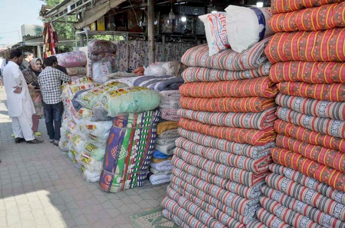 ISLAMABAD: October 18 – Vendor displaying quilts to attract the customers at stall in Sunday Bazaar. APP photo by Saleem Rana