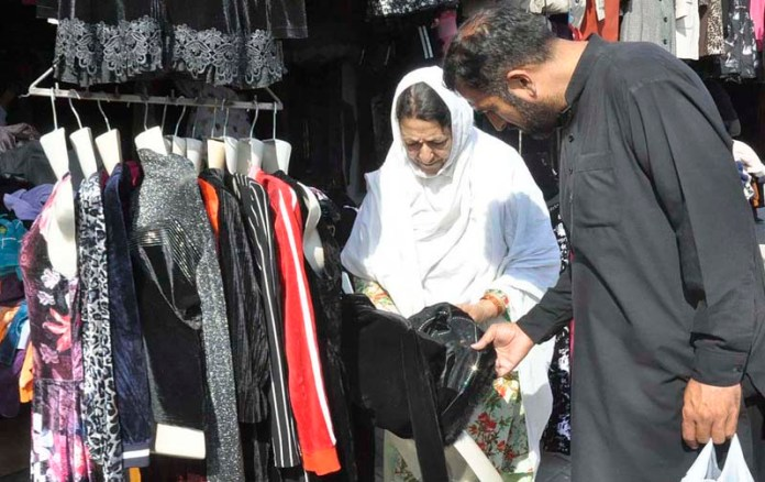 ISLAMABAD: October 18 – A woman busy in selecting clothes from vendor in Sunday Bazaar. APP photo by Saleem Rana