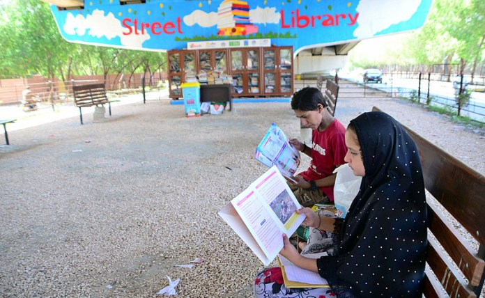 HYDERABAD: October 08 – Children reading books getting from a street library setup under the flyover at Thandi Sarak. APP photo by Farhan Khan