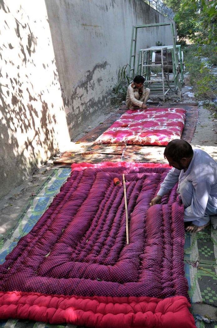 ISLAMABAD: October 05 – Workers busy in preparing quilts as the temperature falls rapidly at night in the federal capital. APP photo by Saeed-ul-Mulk