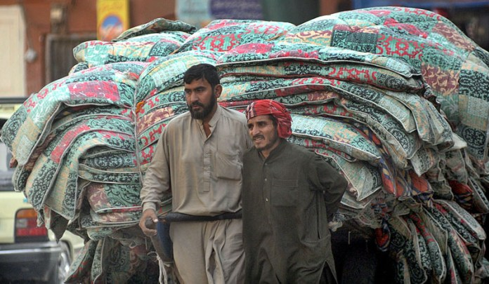 RAWALPINDI: October 31 – Two labourers pulling a hand cart loaded with quilts to supply to markets. APP