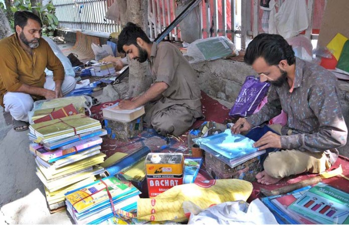 ISLAMABAD: October 05 – Workers busy in binding book covers for school children along the roadside in a local market at G-6. APP photo by Saeed-ul-Mulk