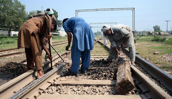 LAHORE: October 08 – Staffers repairing rail tracks near Kot Lakhpat Station. APP photo by Ashraf Ch