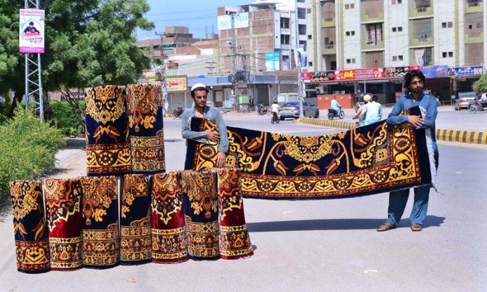 HYDERABAD: October 04 – A vendor displaying carpets to attract the customers at his roadside setup. APP photo by Farhan Khan