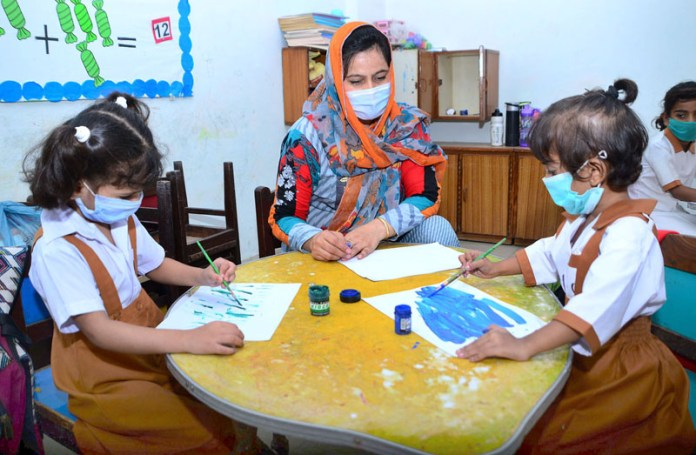 HYDERABAD: October 05 – Junior Primary students attending class with wearing protective facemasks at R.C school as a large number of the students resumed their academic activities after reopening of Primary Education Institutions in the country after around six-month long closure due to the corona virus pandemic. APP photo by Farhan Khan