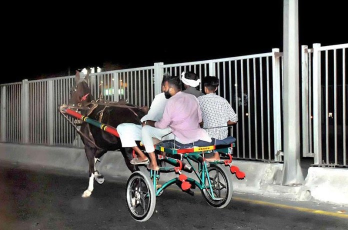 LAHORE: October 22 - People traveling on horse driven cart normally used during races. APP photo by Ashraf Ch