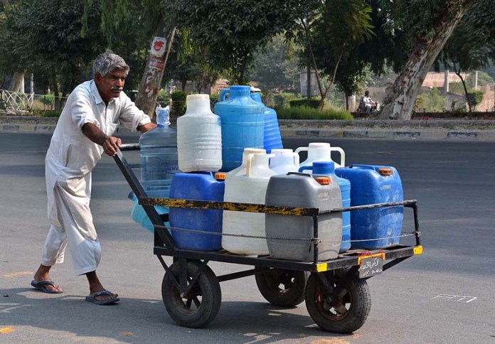 FAISALABAD: October 26 - An elderly person pushing handcart loaded with water bottles after filling from water pumps installed at Rakh Branch Canal to supply it to various houses. APP photo by Tasawar Abbas