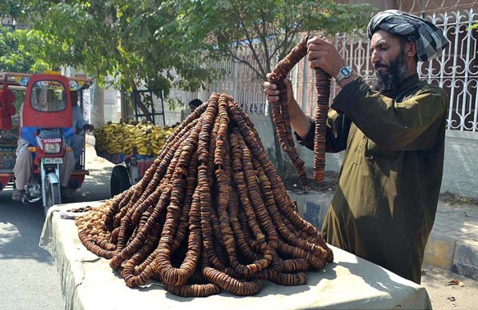 MULTAN: October 06 - A vendor displaying and arranging figs to attract the customers. APP photo by Safdar Abbas