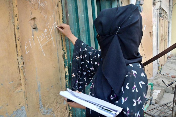 LAHORE: October 28 – A health worker marking the house after administering anti polio drops to child during 5-day Anti-Polio Drive. APP photo by Ashraf Ch