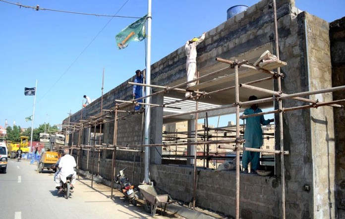 KARACHI: October 05 - Laborers busy in development work of a station being built in connection with Green Line Bus Rapid Transit Project. APP photo by Syed Abbas Mehdi