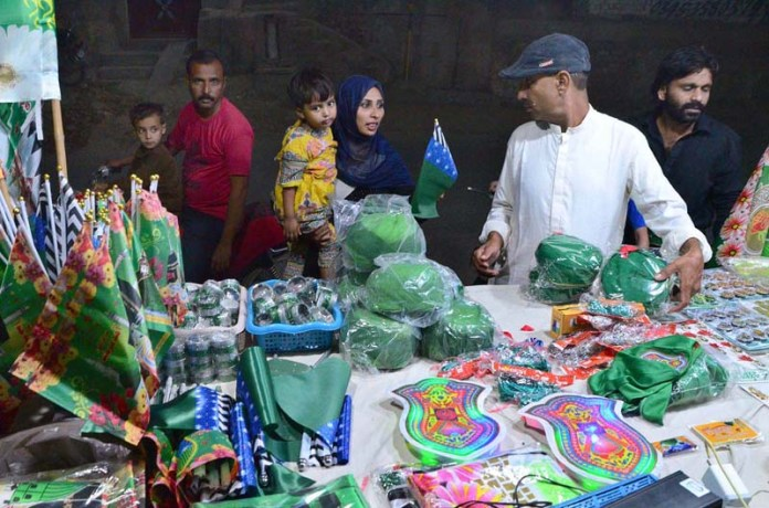 HYDERABAD: October 29 – A lady selecting Eid-e-Milad-un-Nabi (PBUH) celebrations related flag from vendor stall. APP photo by Farhan Khan