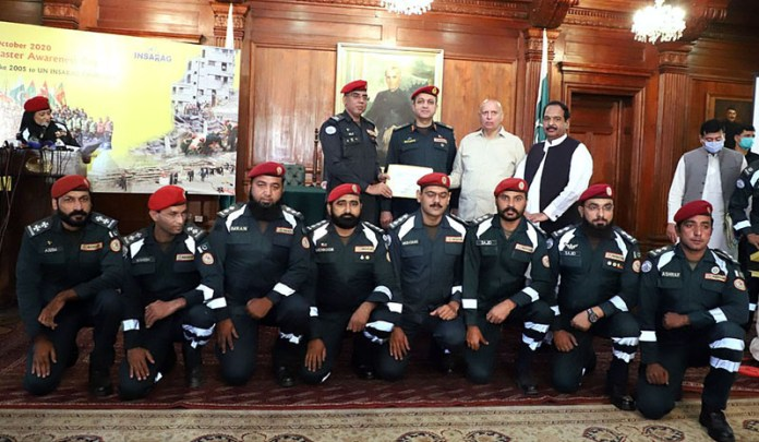 LAHORE: October 08 – Punjab Governor Chaudhry Muhammad Sarwar distributing certificates among different rescue teams during the