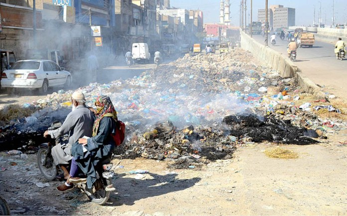 KARACHI: October 21 – A view of burning heap of garbage at main Liaquatabad area creating pollution in the area and needs the attention of concerned authorities. APP photo by Abbas Mehdi