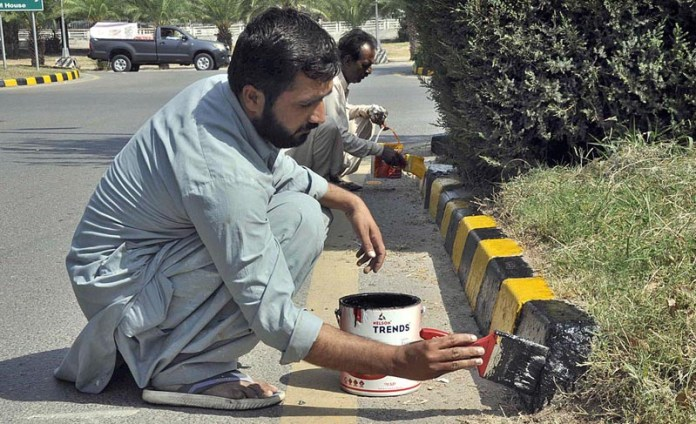 ISLAMABAD: October 09 – Labourers busy in painting roadside blocks in the federal capital. APP photo by Saleem Rana
