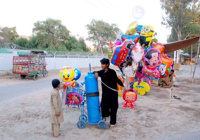 BAHAWALPUR: October 12 – Gas filled toys are being sold out on roadside in Bahawalpur. APP photo by Hassan Bukhari