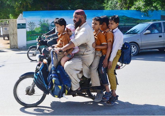 HYDERABAD: October 28 – A motorcyclist on the way with his five children at Hilltop Road. APP photo by Farhan Khan
