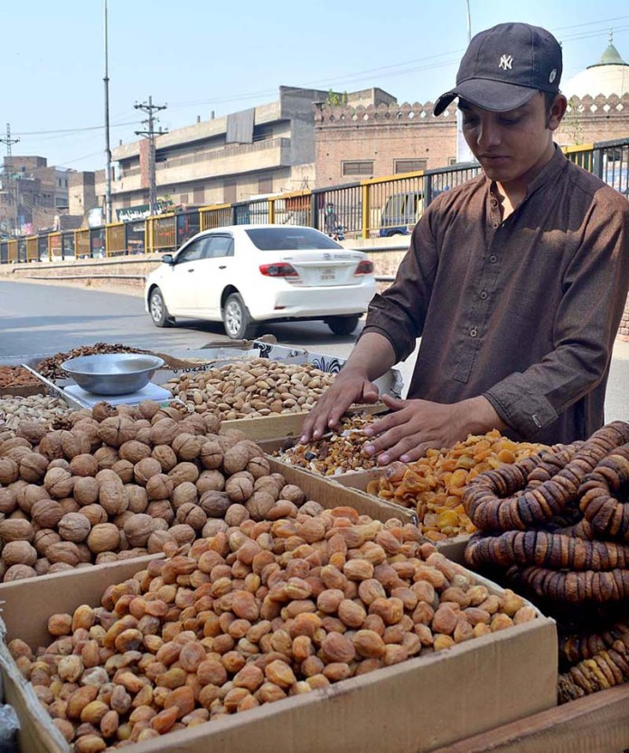 SARGODHA: October 13 – A street vendor displaying different kind of dry fruits to attract the customers. APP photo by Hassan Mahmood