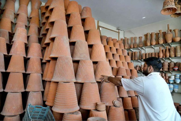LAHORE: October 29 – A vendor arranges earthenware pots at his ware house. APP photo by Amir Khan