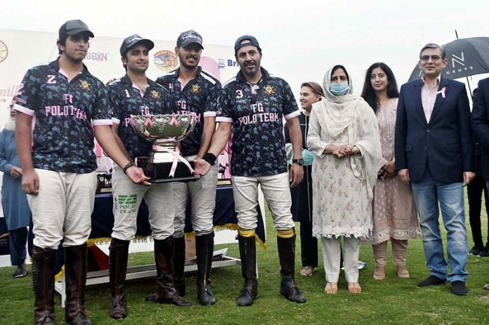 LAHORE: October 24 - Punjab Governor's wife Perveen Sarwar in a group photograph with winning team FG Polo team during prize distribution ceremony of Lulusar Polo in Pink 2020. APP Photo by Rana Imran