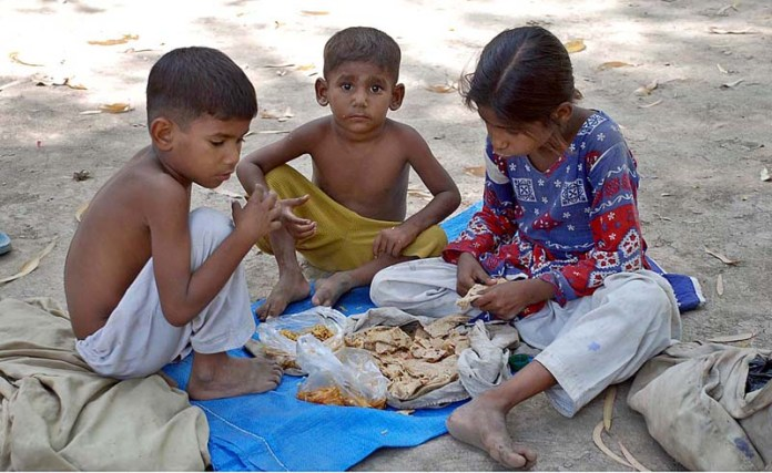 SARGODHA: October 13 – Gypsy children eating their lunch while sitting in Company Bagh. APP photo by Hassan Mahmood