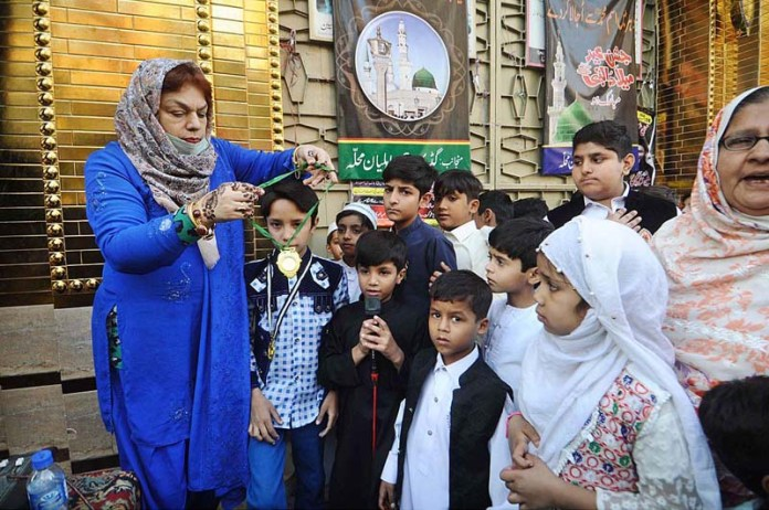 RAWALPINDI: October 30 – A lady awarding medals to naat khawan children during Eid Milad-un-Nabi (PBUH) procession to celebrate birthday of Holy Prophet Muhammad (Peace Be Upon Him). APP photo by Irfan Mahmood