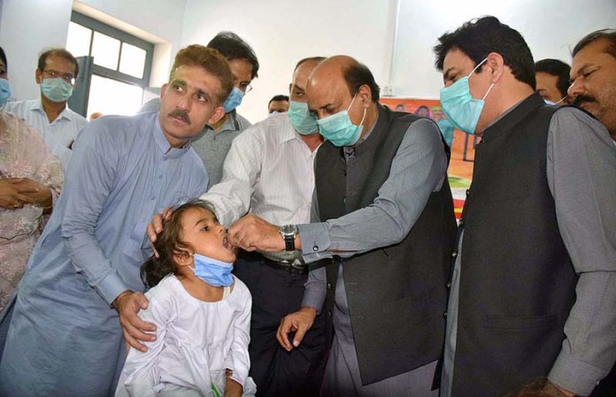 SIALKOT: October 26 – Provincial Minister for Special Education Punjab Ch. Muhammad Akhalaq and DC Zeshan Javaid administering anti polio drops to kick-off anti-polio campaign at Government Girls High School. APP photo by Muhammad Munir Butt