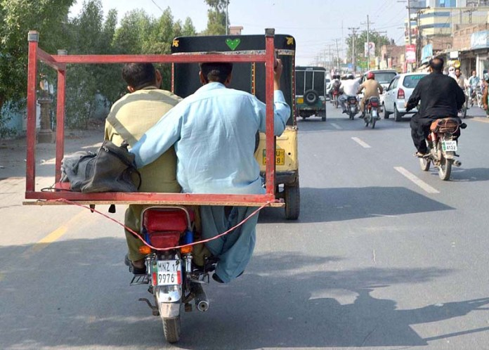 MULTAN: October 26 - A person holding table while sitting on the rear seat of motorcycle. APP photo by Safdar Abbas