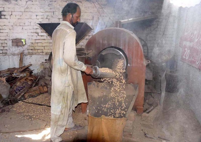 SIALKOT: October 19 - Laborer roasting peanut with the help of machine at his work place. APP photo by Muhammad Munir Butt