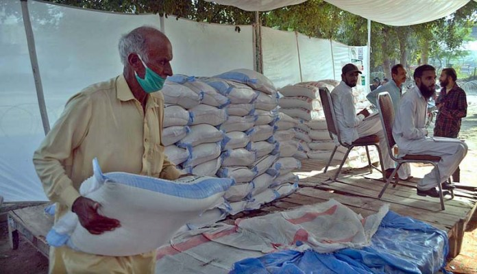 SARGODHA: October 21 – A person carrying flour bag after purchasing from Sahulat Bazaar at Company Bagh. APP photo by Hassan Mahmood