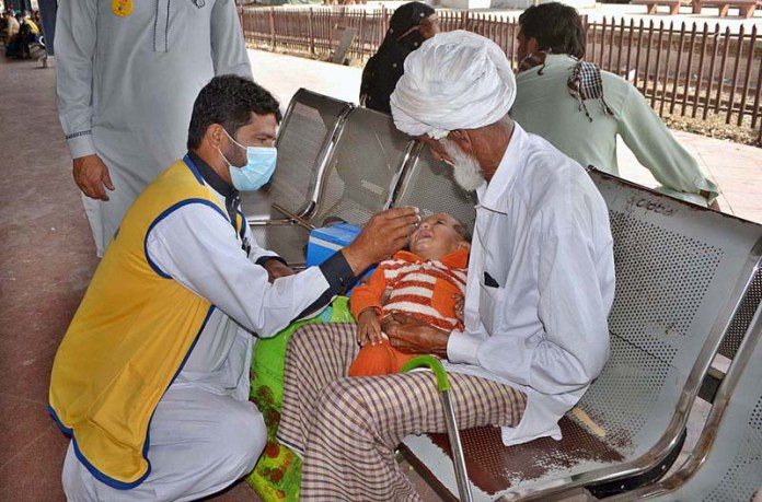 MULTAN: October 26 - A health worker administering anti polio drops to child at Cantt Railway Station during 5-day Anti-Polio Drive. APP photo by Safdar Abbas