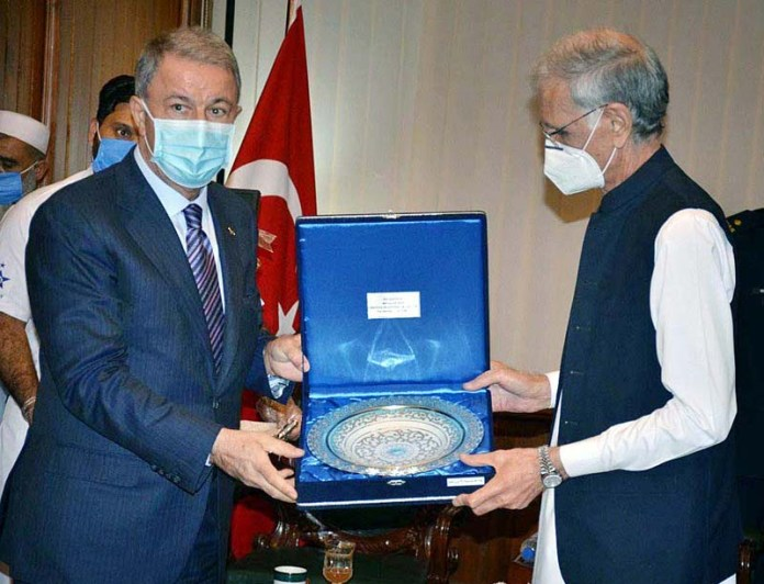 ISLAMABAD: October 25 - Turkish Defence Minister, H.E. Gen (Retd) Hulusi AKAR presenting a gift to Minister for Defence, Pervez Khattak in his office. APP