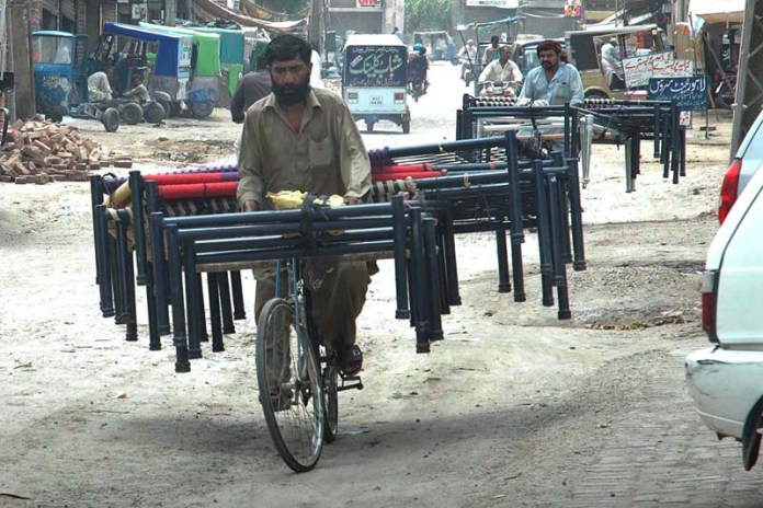 MULTAN: October 05 - Cyclists on the way loaded with frames of traditional bed (Charpai). APP photo by Safdar Abbas