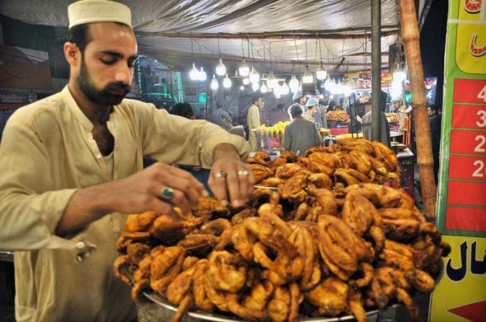 ISLAMABAD: November 10 – A vendor displaying roasted chicken to attract the customers in Federal Capital. APP photo by Saeed-ul-Mulk