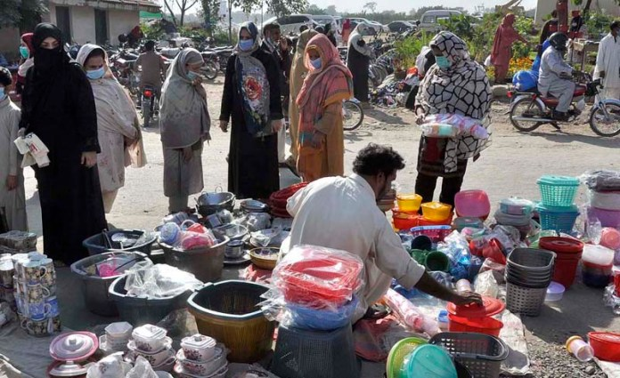 ISLAMABAD: November 01 - Women selecting and purchasing house hold item from vendor at Sunday Bazaar. APP photo by Saleem Rana