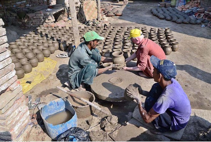 Artisans busy in preparing clay-made stuff at their workplace in Kumharpara at Jamshoro Road