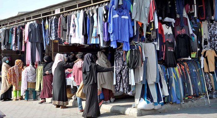 Vendors displaying different kind of dresses to attract the customers at their stalls at weekly Friday Bazaar
