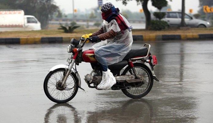 A motorcyclist on the way under the cover of plastic sheet to protect them from rain