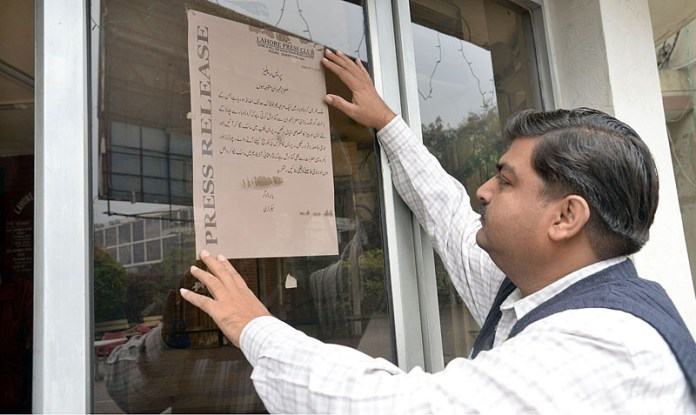 Salman Ahmed, Manager of Press Club placing awareness posters to protect journalists from corona virus (COVID -19)