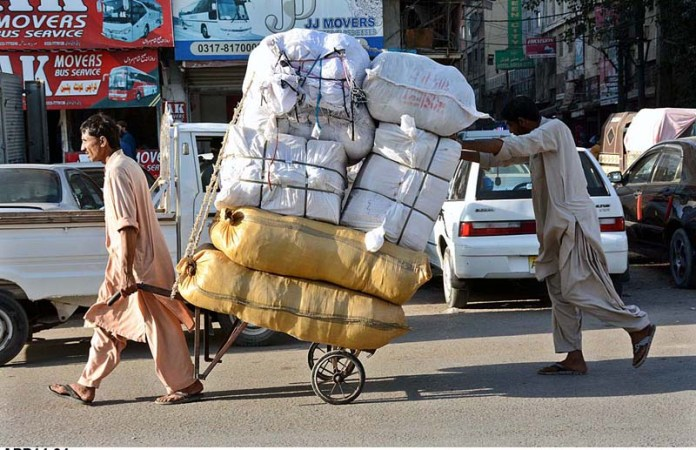 KARACHI: November 04 - Labourers pulling and pushing handcart loaded with luggage to deliver in a local market. APP Photo by M Saeed Qureshi