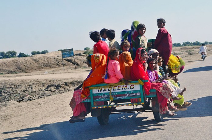 UMERKOT: November 10 – Women with large number of children traveling on tri-cycle rickshaw at Bachao Band Village Road. APP photo by Farhan Khan
