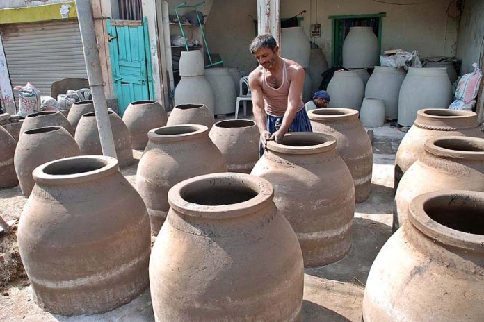 SARGODHA: November 05 - A labourer preparing traditional ovens (tandor) at Railway Chowk. APP photo by Hassan Mahmood