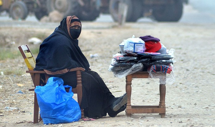 A female vendor waiting for customer to sell different items at her roadside setup