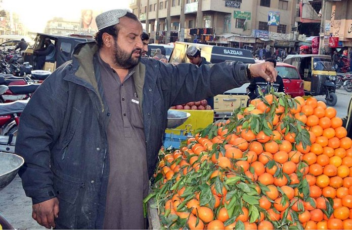 A vendor displaying and arranging oranges to attract the customers on his cart