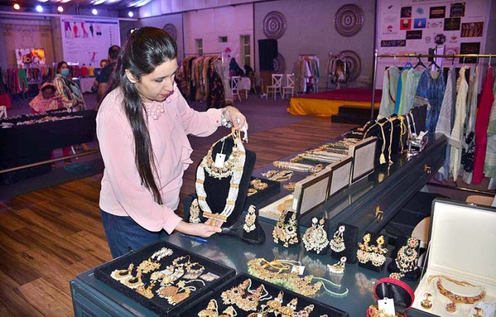 FAISALABAD: November 10 – Women viewing artificial jewelry on stall during clothes exhibition. APP photo by Tasawar Abbas