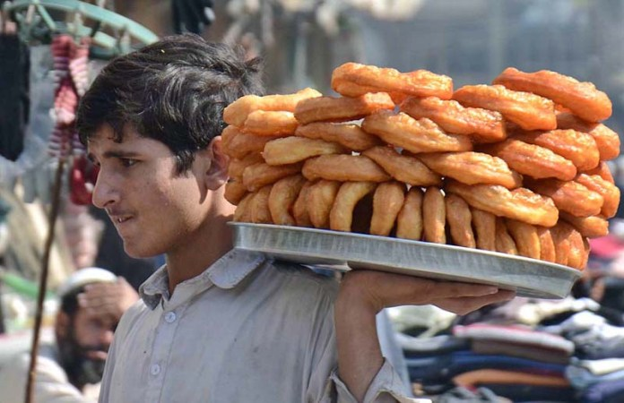 PESHAWAR: November 03 – A young vendor displaying traditional sweet item to attract the customers while shuttling in a local market in Hashtnagri area. APP Photo by Shaheryar Anjum