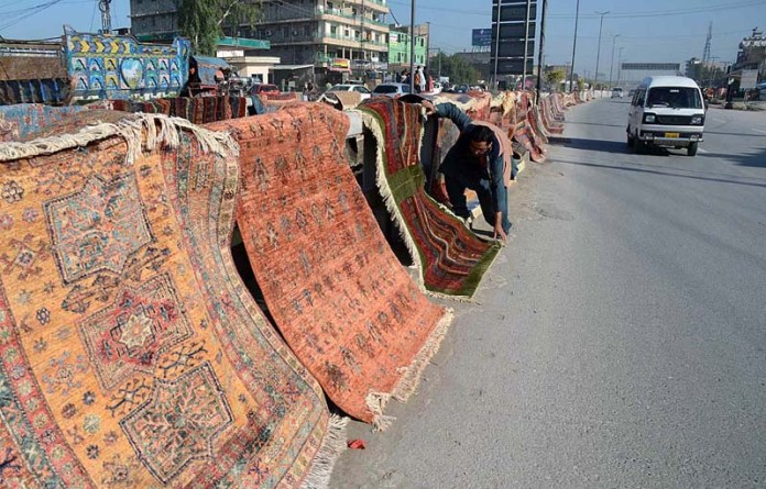 A vendor hanging carpets on cemented blocks at center path of road at Patang Chowk area after washing in factory