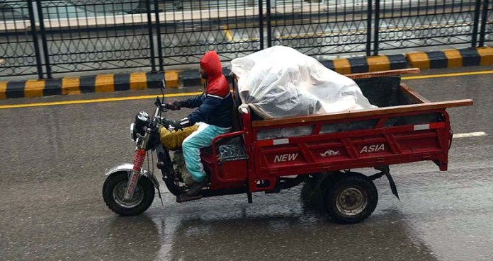 A tri-wheeler loader on the way under the cover of plastic sheet during rain