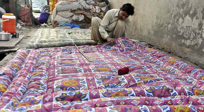 A worker preparing quilts at his workplace